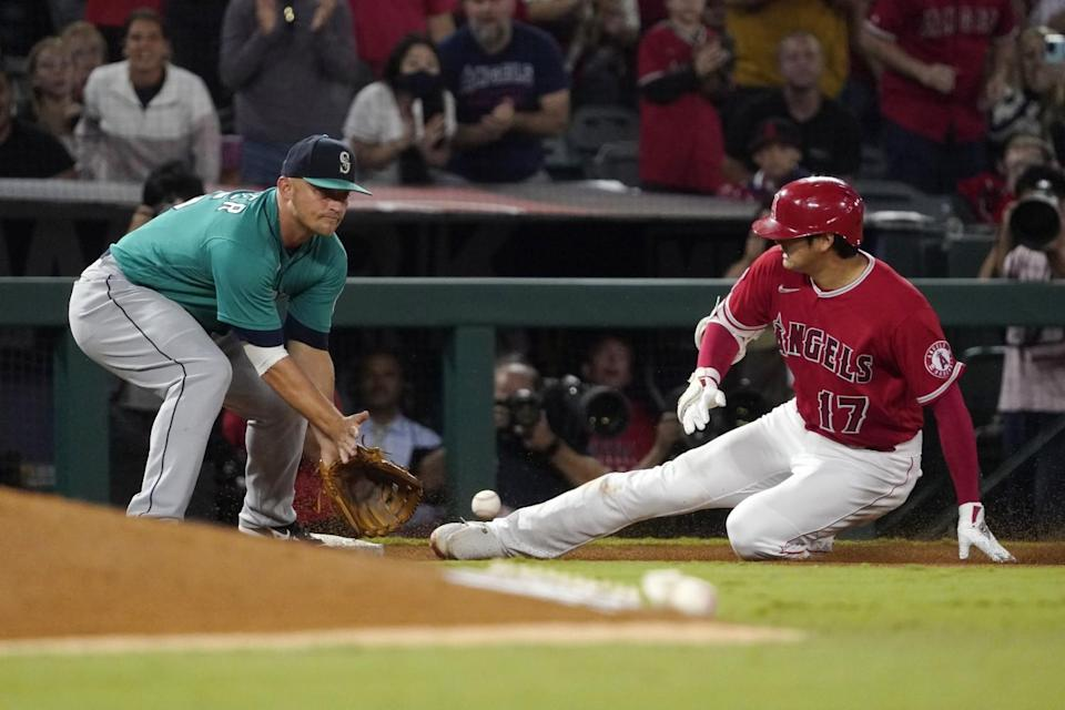 The Angels' Shohei Ohtani slides in for a third-inning triple ahead of the tag of the Mariners' Kyle Seager.