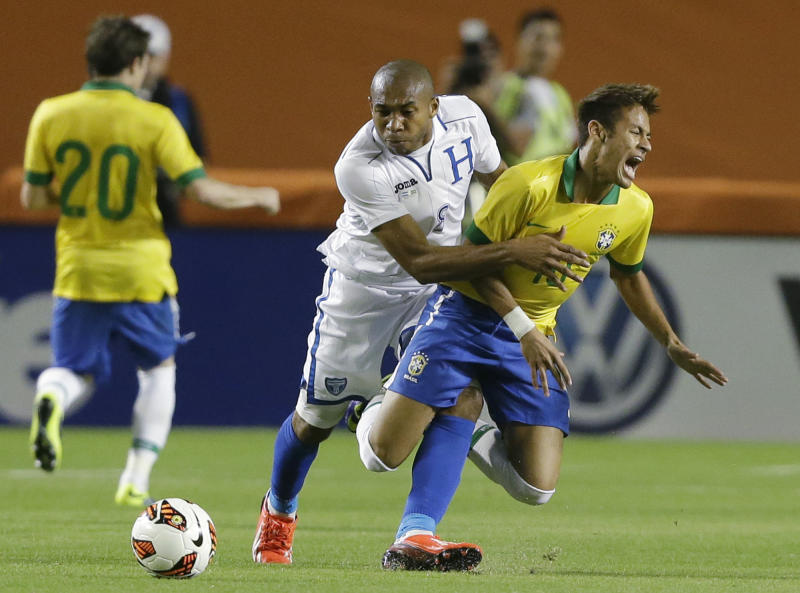 Brazil forward Neymar, foreground, goes down as he battles for the ball with Honduras midfielder Wilson Palacios during the first half of an international friendly soccer game, Saturday, Nov. 16, 2013, in Miami Gardens, Fla. Palacios received a yellow card warning on the play. (AP Photo/Wilfredo Lee)