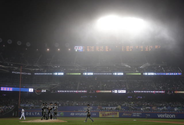 The Arizona Diamondbacks await a pitching change as fog hangs over CitiField during the sixth inning of a baseball game against the New York Mets, Saturday, May 19, 2018, in New York. (AP Photo/Julie Jacobson)