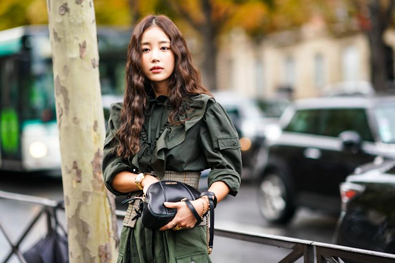 PARIS, FRANCE - OCTOBER 01: A guest wears a long sleeves deep-khaki frilly shirt, khaki pants, a sand color Prince of Wales check lace-up corset belt, a black Miu Miu bag, outside Miu Miu, during Paris Fashion Week - Womenswear Spring Summer 2020, on October 01, 2019 in Paris, France. (Photo by Edward Berthelot/Getty Images)