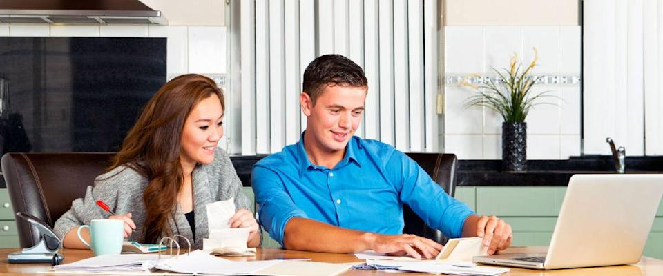 Young couple at the kitchen table, going over their expenses, loans, financial situation and mortgage statements