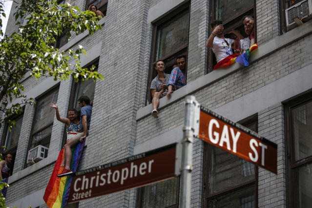 <p>Revelers watch the annual Pride Parade from windows on June 24, 2018 in New York City. (Photo: Kena Betancur/Getty Images) </p>