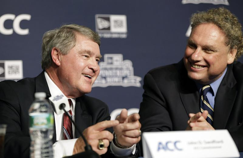 Atlantic Coast Conference Commissioner John Swofford, left, chats with New York Yankees baseball president Randy Levine during a news conference in which the Yankees and the college football Pinstripe Bowl announced a multi-year partnership with the ACC at Yankee Stadium, Tuesday, June 25, 2013, in New York. (AP Photo/Kathy Willens)