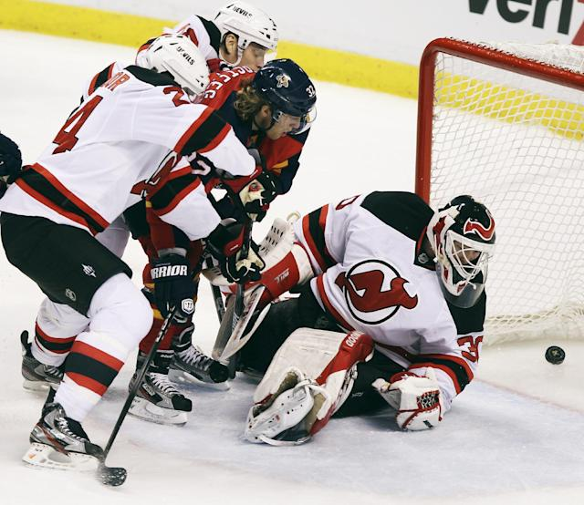 Florida Panthers' Kris Versteeg (32) skates between New Jersey Devils goalie Martin Brodeur (30), Bryce Salvador (24) and Anton Volchenkov (28) to score during the second period of Game 1 of an NHL hockey Stanley Cup first-round playoff series in Sunrise, Fla., Friday, April 13, 2012. (AP Photo/J Pat Carter)