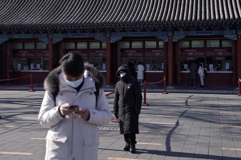 A man wearing a face mask to help curb the spread of the coronavirus browses his smartphone as a masked security guard stands near the quiet ticket counters at the Forbidden City in Beijing, Sunday, Jan. 10, 2021. More than 360 people have tested positive in a growing COVID-19 outbreak south of Beijing in neighboring Hebei province. (AP Photo/Andy Wong)