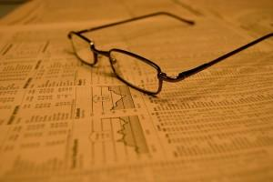 Glasses resting on stock market page