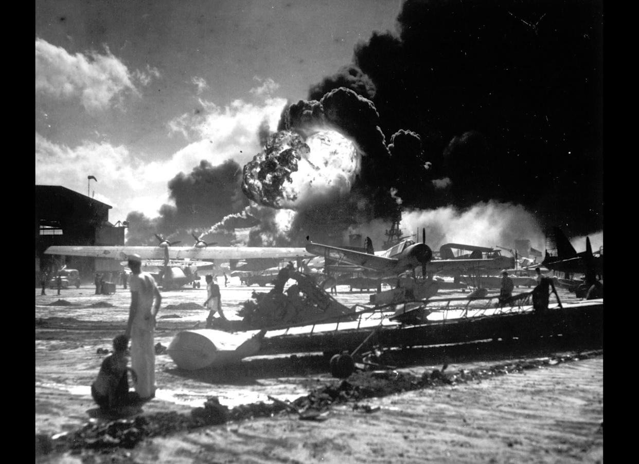 Sailors stand among wrecked airplanes at Ford Island Naval Air Station as they watch the explosion of the USS Shaw in the background, during the Japanese surprise attack on Pearl Harbor.