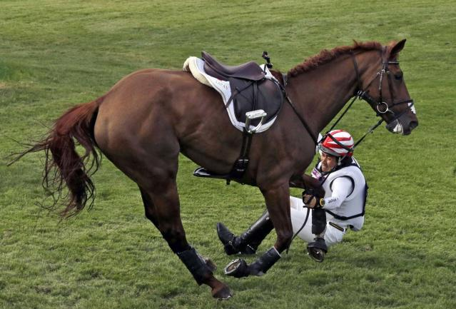 Yoshiaki Oiwa of Japan riding Noonday de Conde falls during competition in the equestrian eventing cross-country stage at the 2012 Summer Olympics, Monday, July 30, 2012, in London. (AP Photo/Ng Han Guan)