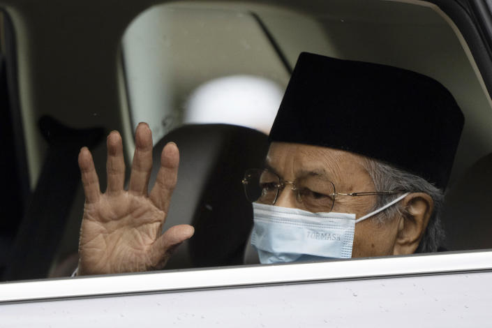 Malaysia's former Prime Minister Mahathir Mohamad, wearing a face mask, waves as he leaves the National Palace after meeting with the king in Kuala Lumpur, Malaysia, Thursday, June 10, 2021. (AP Photo/Vincent Thian)