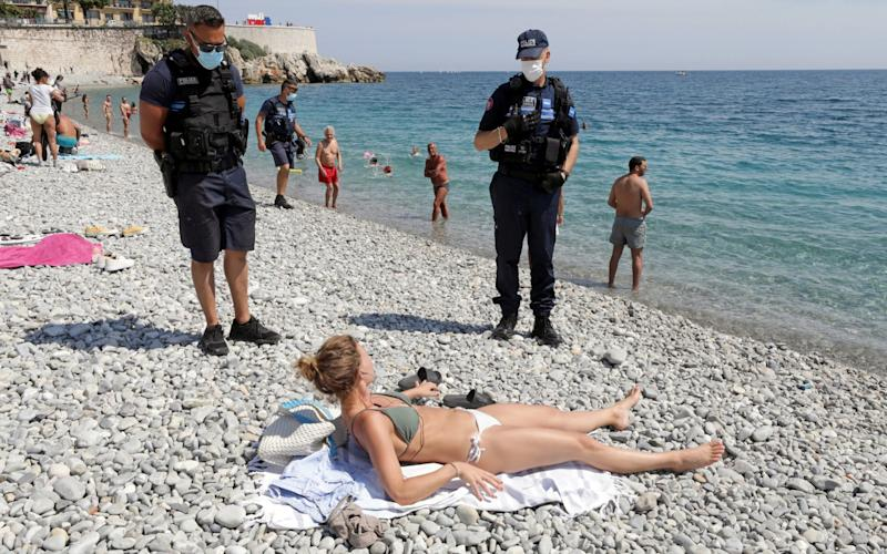 Municipal police officers wearing face masks talk to a woman, at the Promenade des Anglais, as they check that safety restrictions are being practised, after France reopened its beaches to the public as part of the softening of its strict lockdown rules - Eric Gaillard/Reuters