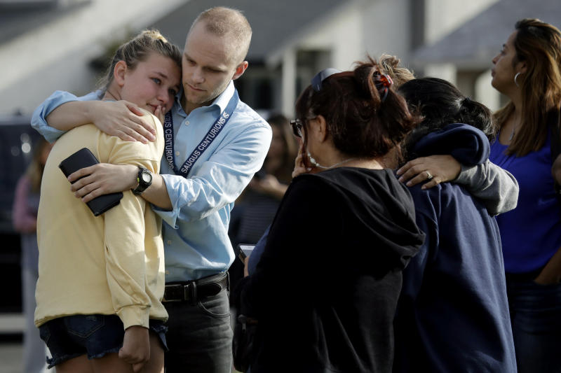 D.J. Hamburger, center in blue, a teacher at Saugus High School, comforts a student after reports of a shooting at the school on Nov. 14, 2019, in Santa Clarita, Calif. (Photo: Marcio Jose Sanchez/AP)