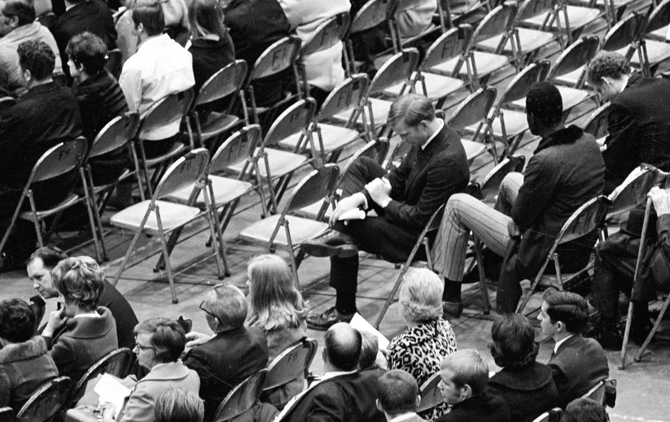 FILE - In this Nov. 15, 1970, file photo, Marshall assistant football coach Red Dawson, center, sits alone during a memorial service at the Veterans Memorial Field House in Huntington, W.Va., honoring the 75 people killed in a plane crash the night before. Marshall will mark the 50th anniversary of the plane crash that killed all 75 aboard on Saturday, Nov. 14, 2020, on the campus in Huntington. (Lee Bernard/The Herald-Dispatch via AP, File)