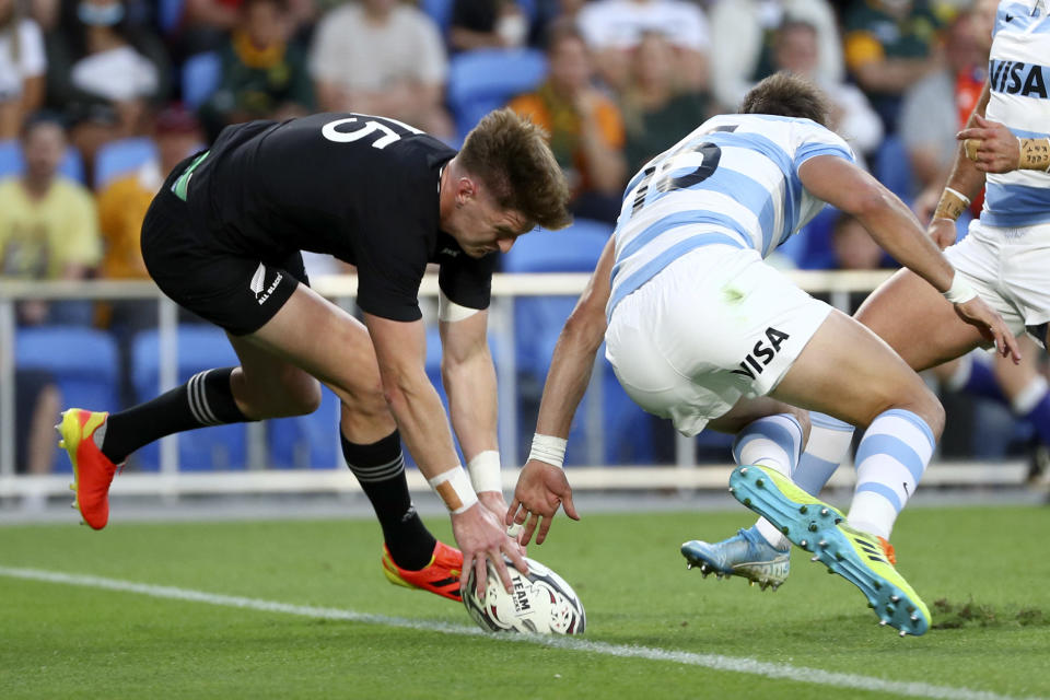New Zealand's Jordie Barrett, left, touches down in a try attempt against Argentina's Juan Cruz Mallia during their Rugby Championship match on Sunday, Sept. 12, 2021, on the Gold Coast, Australia. (AP Photo/Tertius Pickard)
