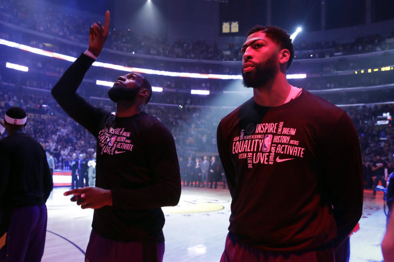 Los Angeles Lakers' Anthony Davis, right, and LeBron James stand during the national anthem before the start of an NBA basketball game against the New Orleans Pelicans Tuesday, Feb. 25, 2020, in Los Angeles. (AP Photo/Marcio Jose Sanchez)