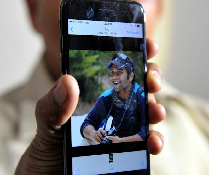 Jagan Mohan Reddy holds a smartphone with an image of his son Alok Madasani at his residence in Hyderabad on February 24, 2017, after Alok was injured in the shooting of two Indian men in the US state of Kansas