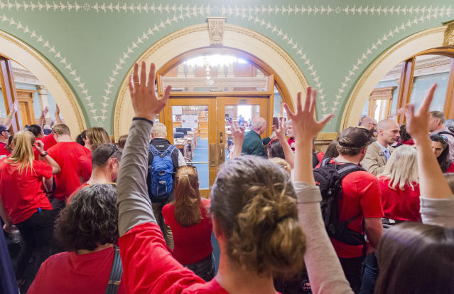 <p>People are dressed in red, many of whom are teachers, show their appreciation as they wave in silent applause from outside of the House of Representatives room in the capital during the deliberation of the measure to offer more support for education as thousands of teachers and supporters rallied in Civic Center Park in Denver, Colo., on Friday, April 27, 2018. (Photo: Dougal Brownlie/The Gazette via AP) </p>