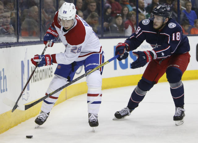 Montreal Canadiens' Mike Reilly, left, clears the puck as Columbus Blue Jackets' Pierre-Luc Dubois defends during the second period of an NHL hockey game Monday, March 12, 2018, in Columbus, Ohio. (AP Photo/Jay LaPrete)
