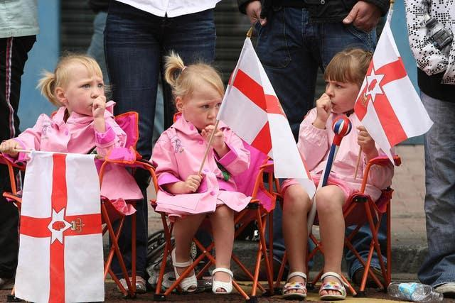 Young girls watch the celebrations in ventral Belfast as the Orange Order and marching bands mark the Battle of the Boyne