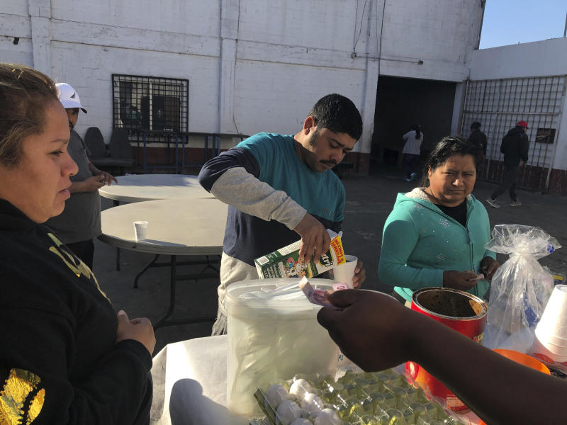 In this Jan. 11, 2020, photo, Joel Caceres, center, pours milk in his coffee as other asylum seekers at a migrant shelter purchase food in Mexicali, Mexico. Caceres, from Honduras, is seeking asylum in San Diego with his wife and two sons. Illegal border crossings have plummeted as the Trump administration has extended a policy to make asylum seekers wait in Mexico for court hearings in the U.S. (AP Photo/Elliot Spagat)