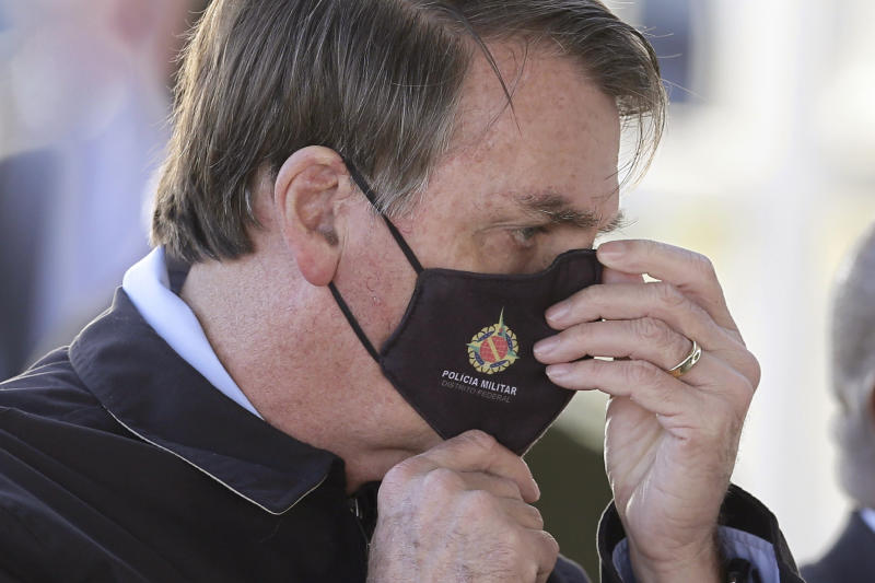 Brazil's President Jair Bolsonaro adjusts his face mask as he speaks to supporters while departing his official residence, Alvorada palace, in Brasilia, Brazil, Thursday, May 21, 2020. (AP Photo/Eraldo Peres)