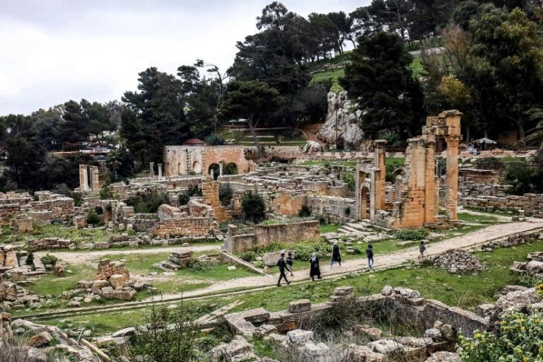 People walk through the remains of the Sanctuary of Apollo in the UNESCO-listed ruins of the ancient city of Cyrene in eastern Libya