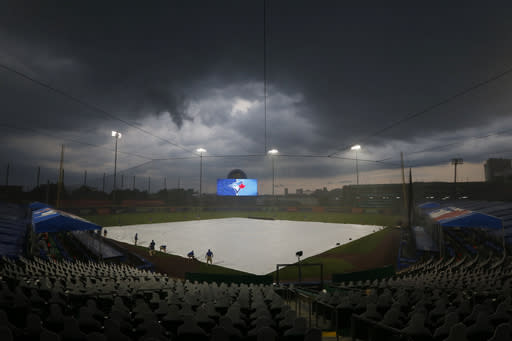 Toronto Blue Jays grounds crew cover field during a rain storm during the fourth inning of a baseball game against the Tampa Bay Rays, Saturday, Aug. 15, 2020, in Buffalo, N.Y. (AP Photo/Jeffrey T. Barnes)