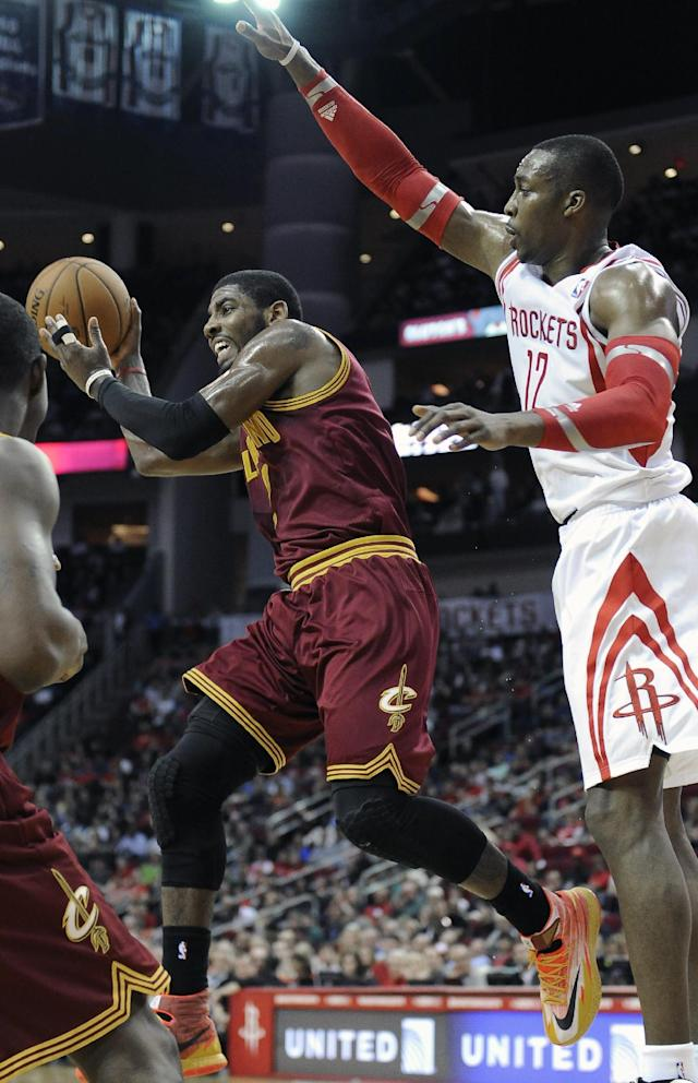 Cleveland Cavaliers' Kyrie Irving, left, passes the ball away from Houston Rockets' Dwight Howard (12) in the first half of an NBA basketball game Saturday, Feb. 1, 2014, in Houston. (AP Photo/Pat Sullivan)