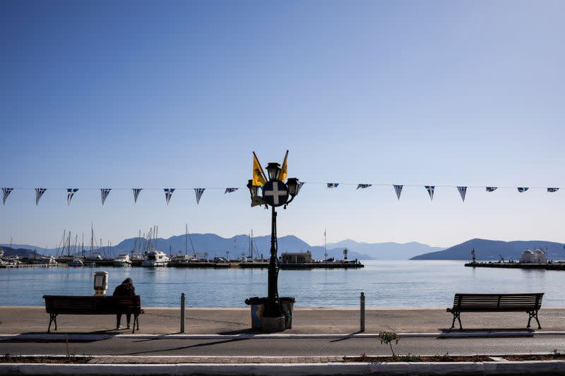 A woman sits on a bench at the promenade, on the island of Aegina