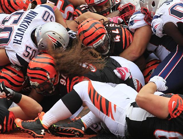 Cincinnati Bengals running back BenJarvus Green-Ellis (42) scores on a 1-yard touchdown run behind a block by Domata Peko (94) in the second half of an NFL football game against the New England Patriots, Sunday, Oct. 6, 2013, in Cincinnati. (AP Photo/Tom Uhlman)