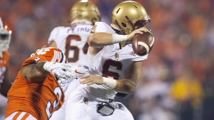 Boston College quarterback Dennis Grosel (6) avoids a tackle by Clemson defensive end Xavier Thomas (3) during the first half of an NCAA college football game, Saturday, Oct. 2, 2021, in Clemson, S.C. (AP Photo/Hakim Wright Sr.)