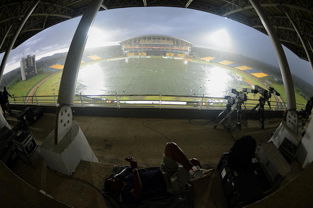 A video cameraman takes a rest after rain stopped play during the second One-Day International (ODI) match between Sri Lanka and Bangladesh at The Suriyawewa Mahinda Rajapakse International Cricket Stadium in the southern district of Hambantota on March 25, 2013.  AFP PHOTO/ Ishara S. KODIKARA        (Photo credit should read Ishara S.KODIKARA/AFP/Getty Images)