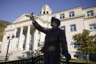 A statue of a coal miner stands in front of the Boone County Courthouse in Madison, W.Va., on Tuesday, Oct. 13, 2020. Four years after Donald Trump donned a miner's helmet at a West Virginia campaign rally and vowed to save a dying industry, coal has not come roaring back. The fuel has been outmatched against cheaper, cleaner natural gas and renewable energy. But many West Virginians applaud Trump's efforts and remain loyal as he seeks a second term. (AP Photo/Chris Jackson)