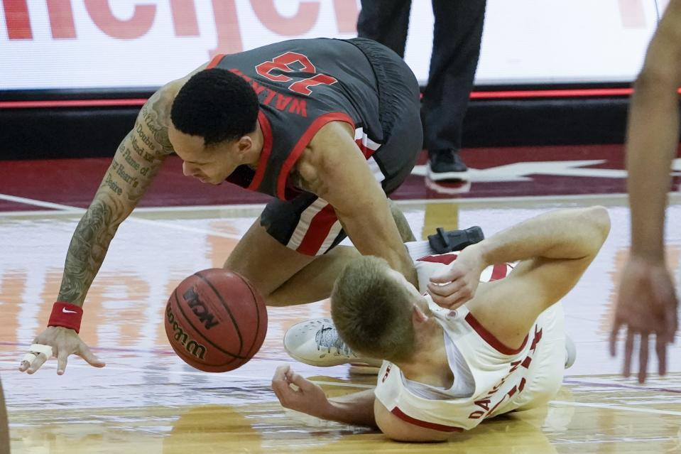 Ohio State's CJ Walker and Wisconsin's Brad Davison go after a loose ball during the second half of an NCAA college basketball game Saturday, Jan. 23, 2021, in Madison, Wis. (AP Photo/Morry Gash)