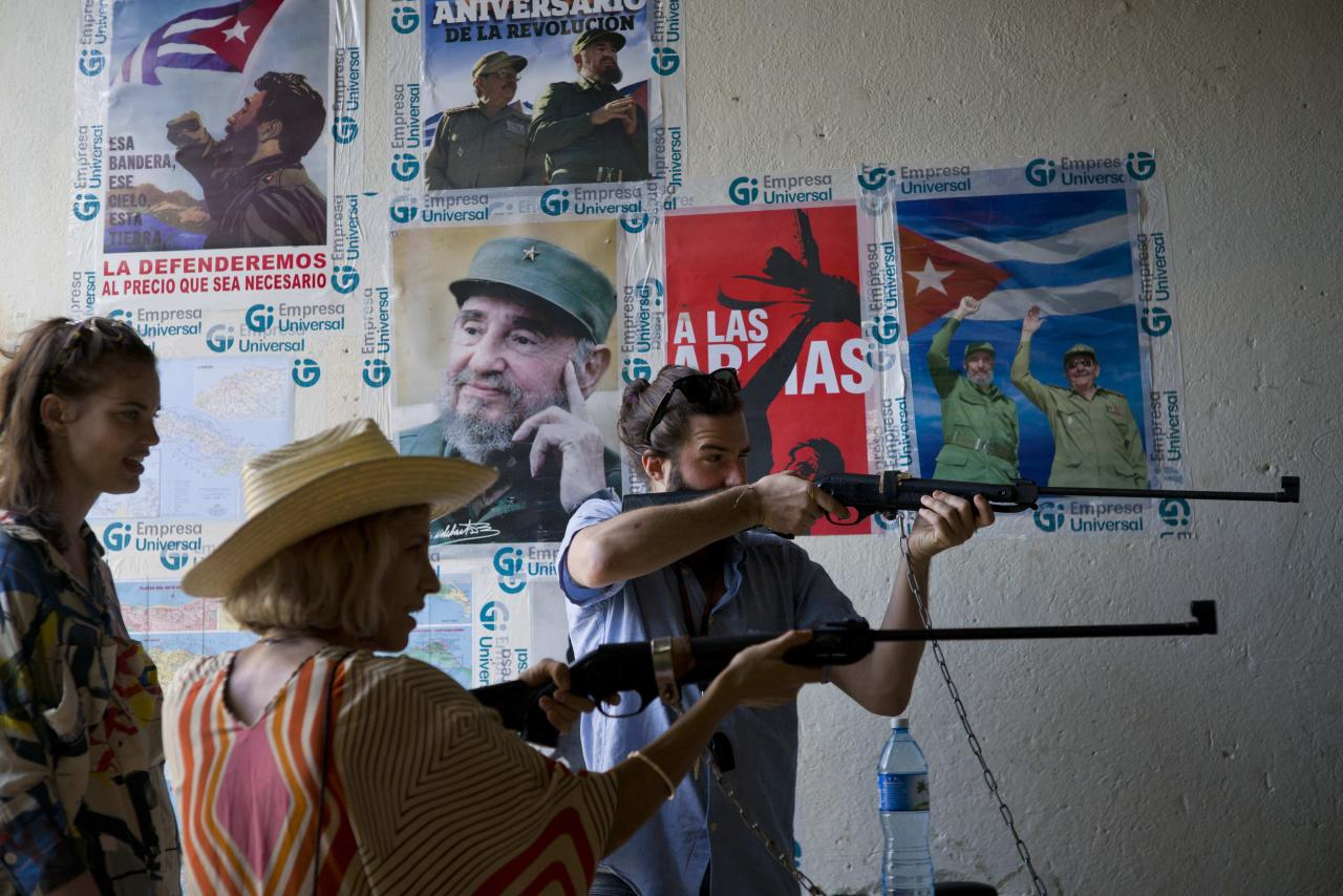 Tourists shoot compressed air rifles next to posters of Cuba'a late leader Fidel Castro at a recreational center in Havana, Cuba, Sunday, Nov. 27, 2016. Cuba's government declared nine days of national mourning after Castro died Friday and this normally vibrant city has been notably subdued. As Cuba prepares a massive commemoration for the leader of its socialist revolution, tens of thousands of tourists find themselves accidental witnesses to history. (AP Photo/Ramon Espinosa)