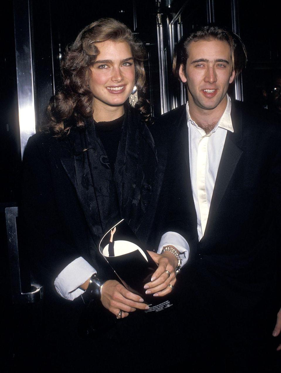 """<p>Here, Brooke is pictured with actor Nicolas Cage at the <em>Moonstruck</em> premiere in New York City. The two briefly <a href=""""https://www.etonline.com/slideshow/gallery/123683_They_Dated_Surprising_Celebrity_Hookups/42900"""" rel=""""nofollow noopener"""" target=""""_blank"""" data-ylk=""""slk:dated"""" class=""""link rapid-noclick-resp"""">dated</a> in the '80s. Brooke has also been <a href=""""https://people.com/celebrity/brooke-shields-husbands-boyfriends-john-travolta-liam-neeson-andre-agassi/"""" rel=""""nofollow noopener"""" target=""""_blank"""" data-ylk=""""slk:linked"""" class=""""link rapid-noclick-resp"""">linked</a> to Scott Baio, John Travolta, Dean Cain, and Liam Neeson. <br></p>"""