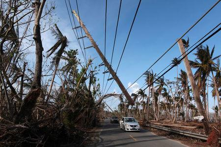 FILE PHOTO: Cars drive under a partially collapsed utility pole, after the island was hit by Hurricane Maria in September, in Naguabo, Puerto Rico October 20, 2017. REUTERS/Alvin Baez/File photo