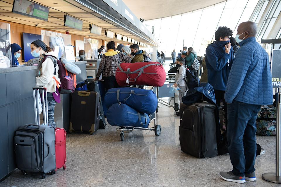 Travelers in face masks stand at a check-in counter surrounded by luggage at Dulles International Airport in Dulles, Va.