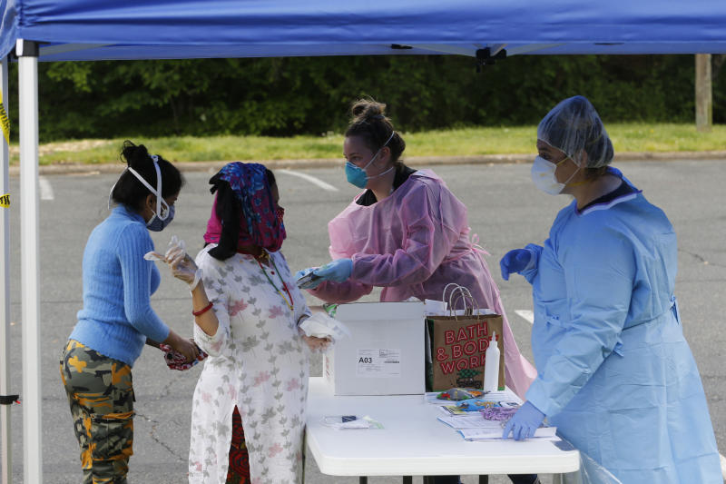 Richmond City Health District workers check in residents for COVID-19 testing at a site set up by the Virginia National Guard Tuesday May 5, 2020, in Richmond, Va. (AP Photo/Steve Helber)
