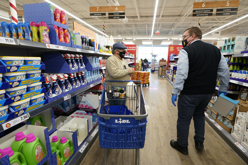 "In this Thursday, Feb. 4, 2021 photo, a customer asks Lidl employee Joseph Lupo, right, for help finding a product inside the Lidl grocery market in Lake Grove, N.Y. Lupo received his first dose of the coronavirus vaccination earlier in the day. The German grocery chain is offering $200 in extra pay to employees willing to get vaccinated against COVID-19. Lupo, a Lidl supervisor who fell ill with the virus in March, was elated to get his first vaccine dose. ""I never ever want to get COVID again, or see anybody else get it,"" said Lupo, 59. (AP Photo/Kathy Willens)"