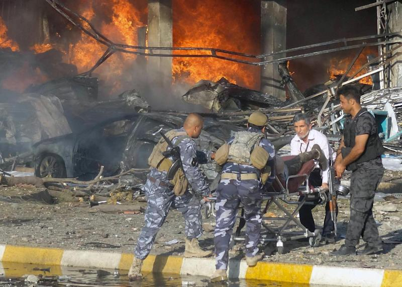Iraqi emergency service personnel at the site of a roadside bomb attack in the Kurdish-controlled northern Iraqi city of Kirkuk on August 23, 2014