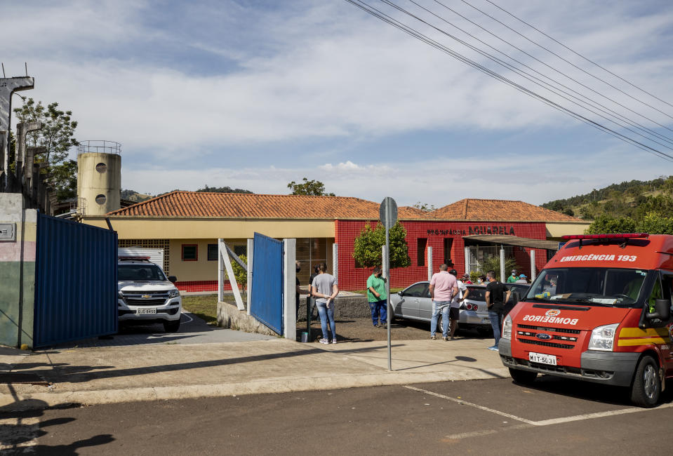 Relatives stand outside the Aquarela preschool in Saudades, in the southern state of Santa Catarina, Brazil, Tuesday, May 4, 2021. According to police an 18-year-old teenager entered the day care center with a knife and stabbed and killed three children and a teacher. (AP Photo/Liamara Polli)