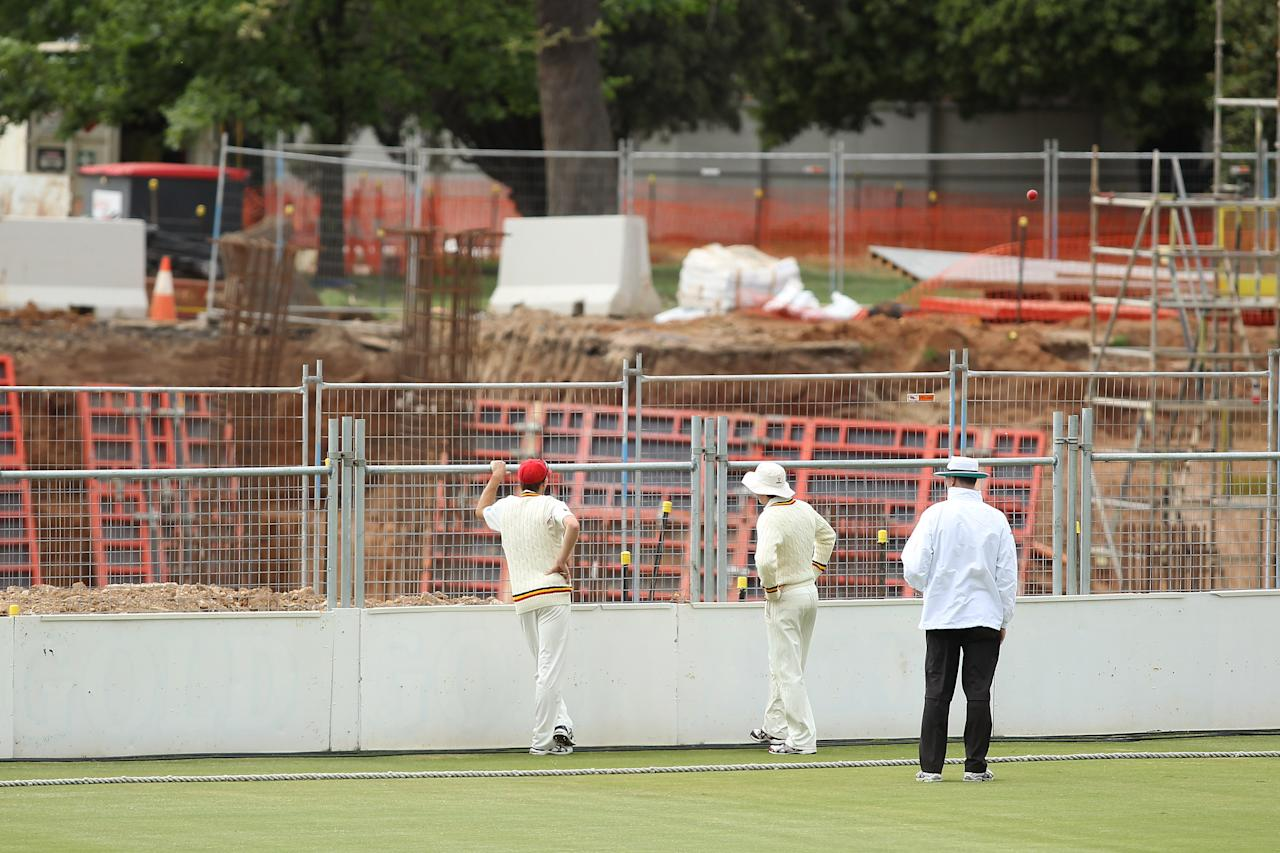 ADELAIDE, AUSTRALIA - OCTOBER 10:  Players and the umpire wait for the ball to be returned from the construction area, after a six was hit over the fence during day two of the Sheffield Shield match between South Australian Redbacks and the Tasmanian Tigers at Adelaide Oval on October 10, 2012 in Adelaide, Australia.  (Photo by Morne de Klerk/Getty Images)