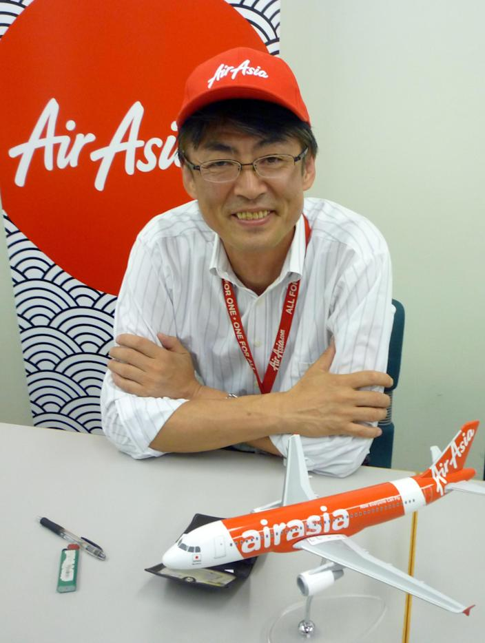 """In this Sept. 28, 2012 photo, AirAsia Japan President Kazuyuki Iwakata smiles during an interview in Tokyo. """"It's not that the meals on standard fares were ever free. The charge was just part of the ticket price,"""" Iwakata told The Associated Press. """"With us, people pay only for what they need."""" As a marketing ploy, AirAsia Japan, which started operations in August, offered tickets for just 5 yen (5 cents) to the first 10,000 people. They quickly sold out. (AP Photo/Yuri Kageyama)"""