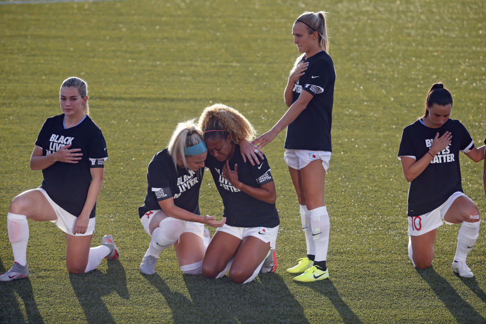 Chicago Red Stars' Julie Ertz, second from left, holds Casey Short, center, while other players for the team kneel during the national anthem before an NWSL Challenge Cup soccer match against the Washington Spirit at Zions Bank Stadium, Saturday, June 27, 2020, in Herriman, Utah. (AP Photo/Rick Bowmer)