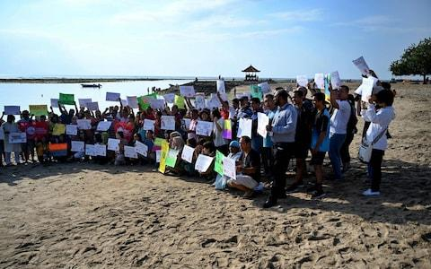 People display placards during a rally as part of a global climate change campaign at Sanur beach on Indonesia's resort island of Bali - Credit: AFP