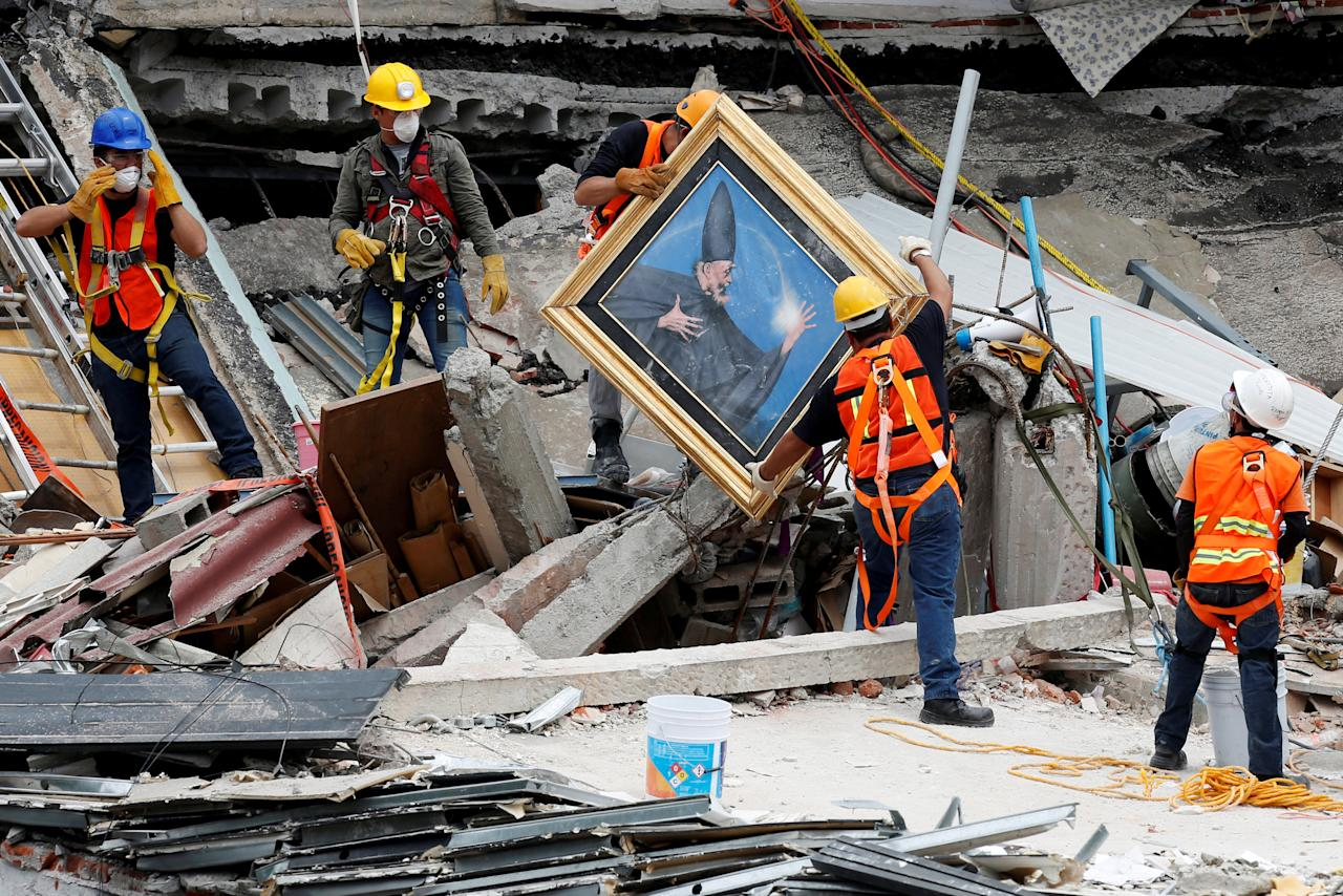 Mexican and international rescue teams remove a painting as they search for survivors in a collapsed building after an earthquake, at Roma neighborhood in Mexico City, Mexico September 23, 2017. REUTERS/Carlos Jasso     TPX IMAGES OF THE DAY