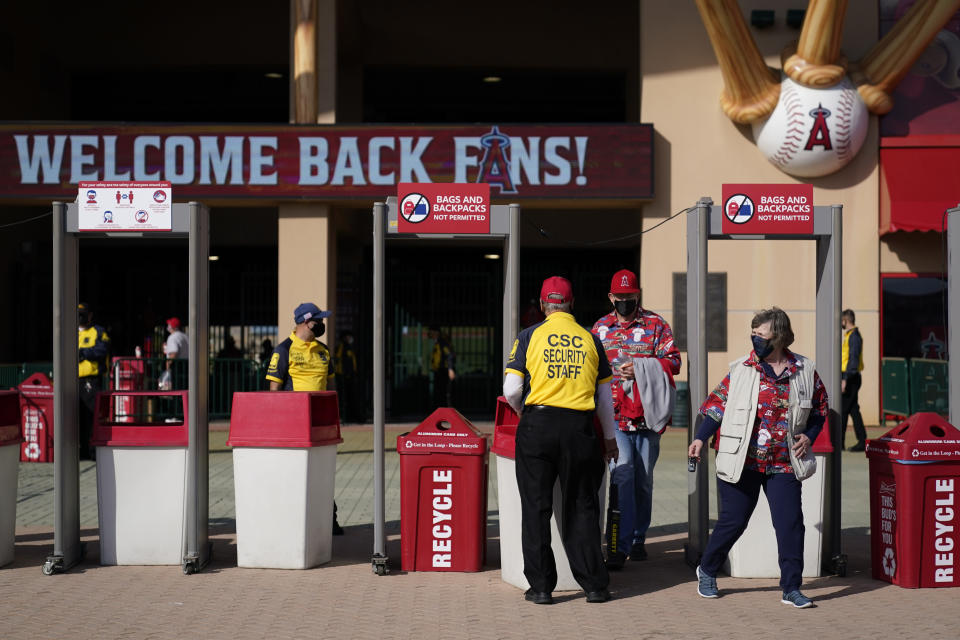 A security guard moves a barrier to allow fans to leave Angel Stadium when a baseball game between the Minnesota Twins and the Los Angeles Angels was postponed Saturday, April 17, 2021, in Anaheim, Calif. MLB said the game was postponed to allow for continued COVID-19 testing and contact tracing involving members of the Twins organization. (AP Photo/Ashley Landis)