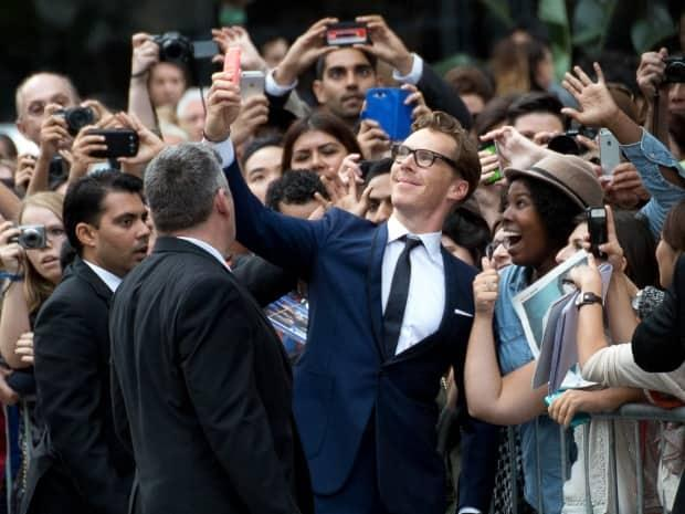 Actor Benedict Cumberbatch poses with fans on the red carpet at TIFF in 2014. He has been named a recipient of this year's TIFF Tribute Actor Award and will attend this year's festival. (David Donnelly/CBC - image credit)