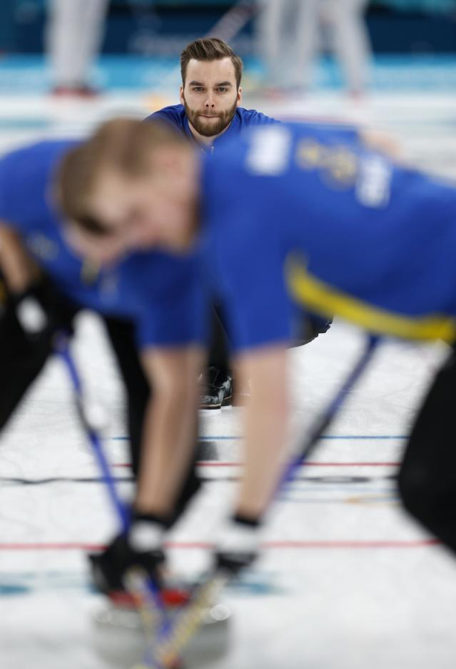 <p>Vice-skip Oskar Eriksson of Sweden watches the shot. REUTERS/John Sibley </p>