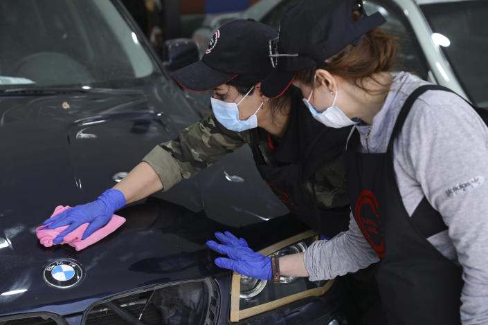 Female car detailer Maryam Roohani polishes a car as her trainee Farahnaz Deravi watches, at a detailing shop in Tehran, Iran, April 18, 2021. The auto industry remains male-dominated around the world, let alone in the tradition-bound Islamic Republic. Still Iranian women, especially in the cities, have made inroads over the years. (AP Photo/Vahid Salemi)